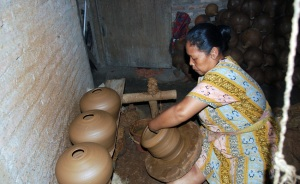 "A woman is making water jars using a traditional wheel called ""perbot""."